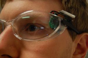 Image: Phillip wearing his wouse prototype, showing the sensor and battery pack attached to the temple of a pair of safety glasses